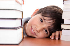 Giovane ragazzo di banco felice circondato dai libri Immagini Stock