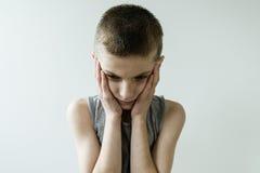 Giovane ragazzo disturbato con la testa e le mani immagini stock