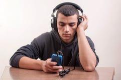 Giovane ragazzo divertendosi come ascolta il suo riproduttore mp3 con grande Immagine Stock