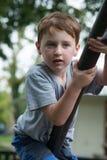 Giovane ragazzo divertendosi fuori al parco su un insieme rampicante del campo da giuoco Fotografia Stock Libera da Diritti