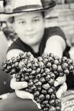 Giovane ragazzo divertente che posa con il mazzo di uva in mani, il nero e Fotografia Stock