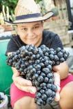 Giovane ragazzo divertente con il mazzo di uva in mani, tema d'annata Immagini Stock