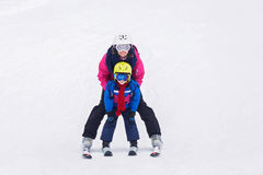 Giovane ragazzo dolce e sua la madre, imparanti sciare su uno sci delicato SL Fotografia Stock Libera da Diritti