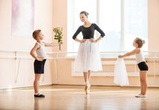 Giovane ragazzo e ragazza che danno i fiori e velo allo studente più anziano mentre sta ballando il pointe dell'en Immagine Stock