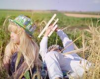 Giovane ragazzo e ragazza che giocano in un giacimento di grano Immagine Stock