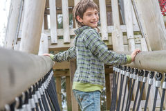 Giovane ragazzo felice al campo da giuoco Fotografie Stock