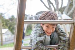 Giovane ragazzo felice al campo da giuoco Fotografia Stock