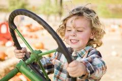 Giovane ragazzo felice che gioca su un vecchio trattore fuori Fotografie Stock Libere da Diritti