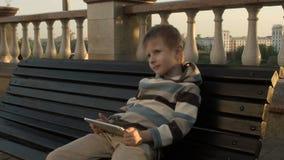 Giovane ragazzo felice che per mezzo del computer della compressa archivi video