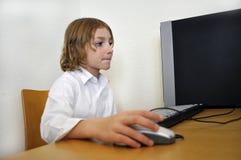 Giovane ragazzo felice che per mezzo di un calcolatore Fotografia Stock