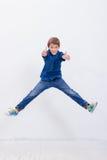 Giovane ragazzo felice che salta sul fondo bianco Immagine Stock