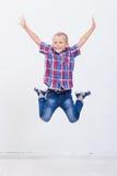 Giovane ragazzo felice che salta sul fondo bianco Fotografia Stock