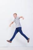 Giovane ragazzo felice che salta sul fondo bianco Fotografia Stock Libera da Diritti