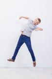 Giovane ragazzo felice che salta sul fondo bianco Fotografie Stock Libere da Diritti