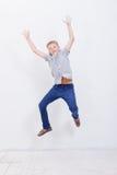 Giovane ragazzo felice che salta sul fondo bianco Fotografie Stock