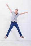 Giovane ragazzo felice che salta sul fondo bianco Immagine Stock Libera da Diritti