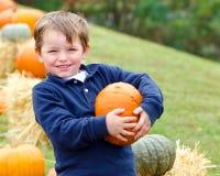 Giovane ragazzo felice che seleziona una zucca Immagini Stock