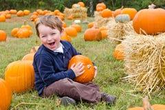 Giovane ragazzo felice che seleziona una zucca Immagini Stock Libere da Diritti