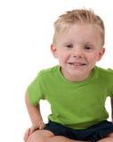 Giovane ragazzo felice che si siede sul bianco Immagine Stock Libera da Diritti