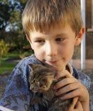 Giovane ragazzo felice con il giovane gattino dell'animale domestico Immagini Stock Libere da Diritti