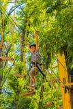 Giovane ragazzo felice del bambino nel parco di avventura in attrezzatura di sicurezza immagine stock libera da diritti