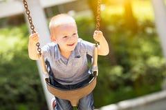 Giovane ragazzo felice divertendosi sulle oscillazioni al campo da giuoco fotografia stock