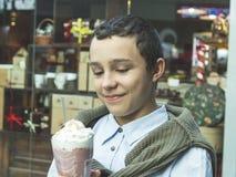 Giovane ragazzo felice sorridente adolescente castana, tenute in mani e bevande un frappé fotografie stock libere da diritti