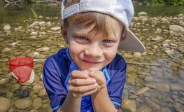 Giovane ragazzo fiero che sta nel fiume con la sua rana immagine stock