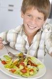 Giovane ragazzo nel sorridere dell'insalata di cibo della cucina fotografia stock