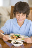 Giovane ragazzo nella sala da pranzo che mangia alimento cinese Immagine Stock