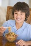Giovane ragazzo nella sala da pranzo che mangia alimento cinese fotografie stock