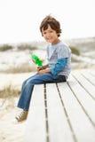 Giovane ragazzo seduto sulla spiaggia con il mulino a vento Immagini Stock