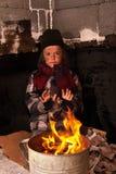Giovane ragazzo senza tetto sulla via che riscalda le sue mani Fotografia Stock