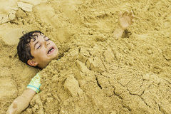 Giovane ragazzo sepolto in sabbia fotografia stock