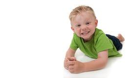 Giovane ragazzo sorridente che pone sul suo stomache Fotografie Stock Libere da Diritti