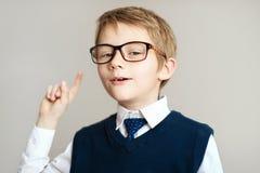 Giovane ragazzo sorridente in grandi vetri che mostrano dito su sopra fondo grigio immagine stock