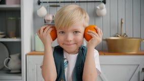 Giovane ragazzo sorridente sveglio con l'arancia sulla cucina, ritratto del bambino, famiglia felice stock footage