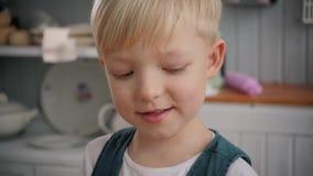 Giovane ragazzo sorridente sveglio sulla cucina, ritratto del bambino, famiglia felice stock footage