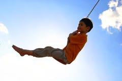 Giovane ragazzo su oscillazione chain Immagini Stock