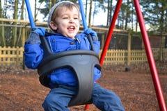 Giovane ragazzo su oscillazione durante l'inverno Immagini Stock
