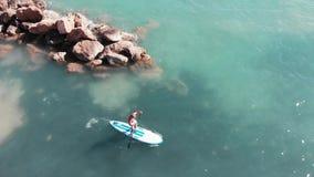 Giovane ragazzo su sup Uomo attraente che pratica il surfing Vista aerea del ragazzo Sun-abbronzato che galleggia sul surf Fuco s video d archivio