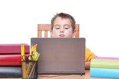 Giovane ragazzo sul computer portatile che studia allo scrittorio con i libri Fotografie Stock