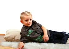 Giovane ragazzo sul pavimento con il cuscino Immagini Stock Libere da Diritti