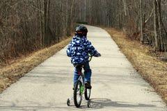 Giovane ragazzo sulla bicicletta con le rotelle di addestramento Fotografie Stock Libere da Diritti