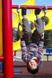 Giovane ragazzo sveglio che appende upside-down su un campo da giuoco Fotografia Stock Libera da Diritti