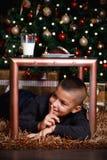 Giovane ragazzo sveglio che aspetta i suoi regali immagini stock libere da diritti