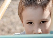 Giovane ragazzo sveglio che esamina la macchina fotografica sul campo da giuoco dei bambini Bambino della scuola materna diverten fotografie stock