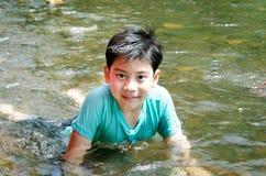 Giovane ragazzo sveglio che gioca nell'acqua in un bello fiume Immagini Stock Libere da Diritti