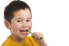 Giovane ragazzo sveglio che pulisce i suoi denti isolati immagini stock libere da diritti