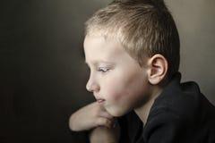 Giovane ragazzo triste della scuola materna che guarda giù e che pensa Bambino infelice con il fronte triste su fondo scuro fotografie stock